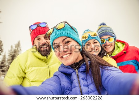 Group of friends taking a selfie - Four snowboarders taking a self portrait with mobile phone - Tourists having fun while skiing - Concepts about winter,christmas,winter vacation and skiing - stock photo