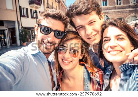 Group of friends taking a selfie - Students smiling at camera and having fun outdoors in a sunny day - Students enjoying the coming of spring - stock photo