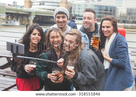 Group of friends taking a selfie with the stick while enjoying a beer at pub in London, toasting and laughing. They are four girls and two boys in their twenties. - stock photo
