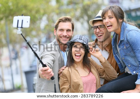 Group of friends taking picture of themselves with smartphone - stock photo