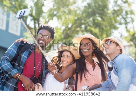 Group of friends taking selfie with selfie stick - stock photo