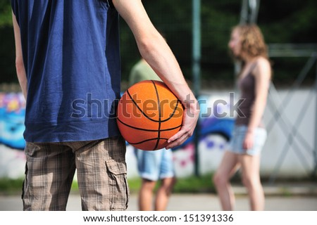 Group of friends talking and taking a break after playing basketball - stock photo