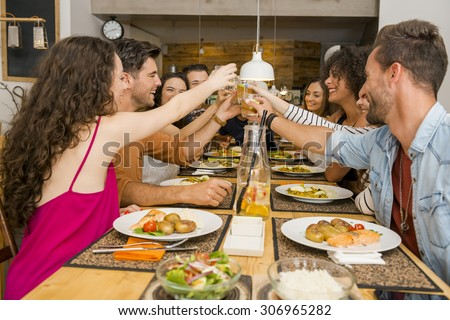 Group of friends toasting and having a good time at the restaurant - stock photo