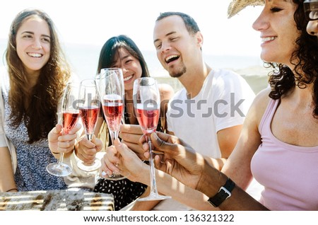 Group of friends toasting champagne sparkling wine at a relax party celebration gathering - stock photo