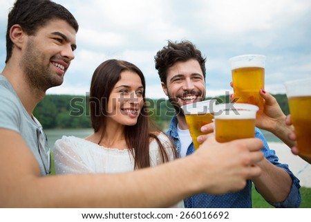 Group of friends toasting with beer in plastic glasses - stock photo
