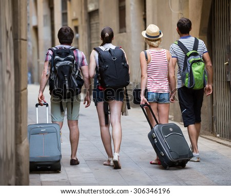 Group of friends tourists walking at the street with luggage  - stock photo