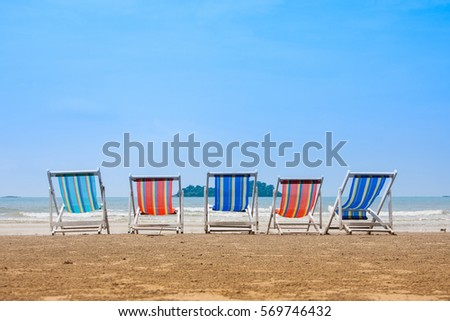 Group of friends travel concept. Group of deck chairs on sunny day at sea beach.