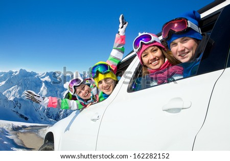 group of friends traveling by car on a vacation to the mountains - stock photo