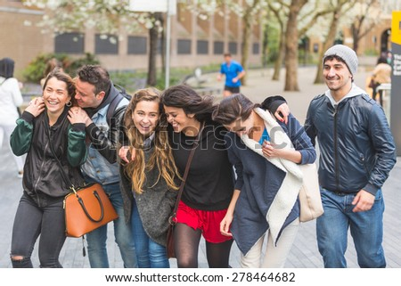 Group of friends walking and having fun together in London. They are four girls and two boys in their twenties, friendship and lifestyle concepts, autumn clothing - stock photo