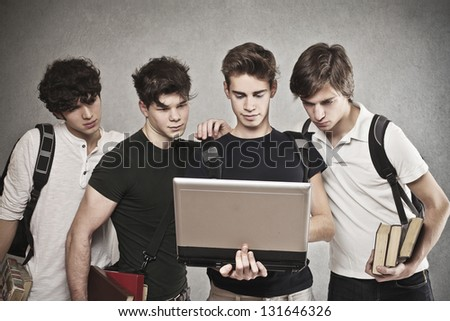 group of friends watching laptop together - stock photo