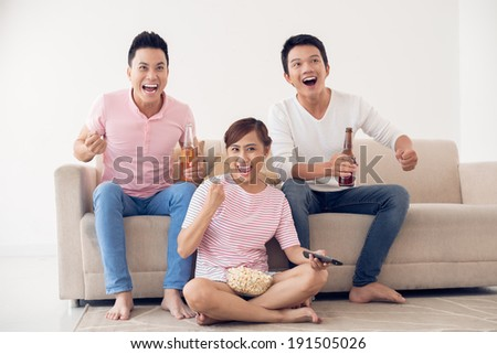 Group of friends watching sport game on tv - stock photo