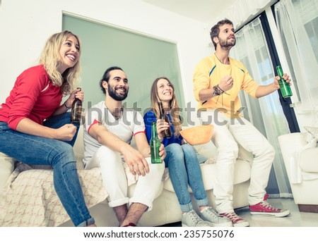 group of friends watching sport match on tv at home. concept about friendship and sport - stock photo
