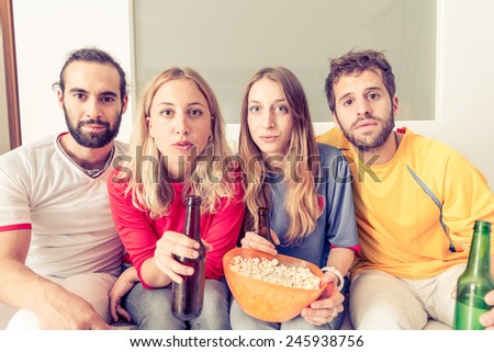 group of friends watching tv with a lot of interest. concept about sport, friendship, and home entertainment - stock photo
