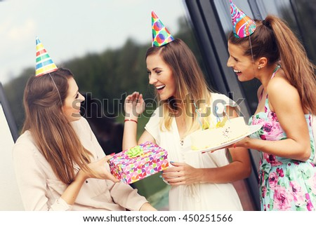 Group of friends with cake and presents celebrating birthday - stock photo