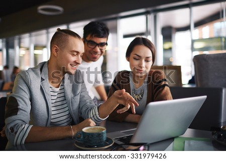 Group of friends with laptop spending leisure in cafe - stock photo