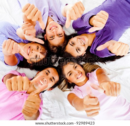 Group of friends with thumbs up lying on the floor - stock photo