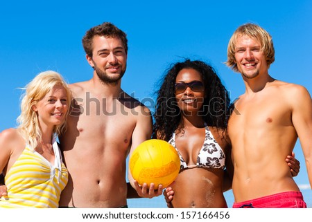Group of friends - women and men - playing beach volleyball, they having a break