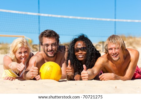 Group of friends - women and men - playing beach volleyball; they having a break and lying in the sun - stock photo