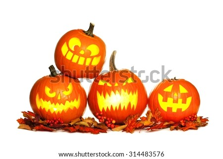 Group of fun lit Halloween Jack o Lanterns with autumn leaves isolated on a white background - stock photo