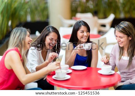Group of girl friends meeting for coffee and talk - stock photo