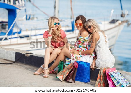 Group of girl friends resting after shopping in the city by the sea, Three young and attractive women are sitting with shopping bags. Pretty girls are having rest after successful shopping day - stock photo