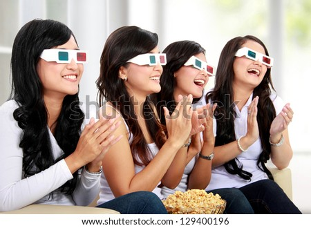 Group of girls clapping watching good 3D movie in home theater - stock photo