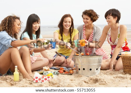 Group Of Girls Enjoying Barbeque On Beach Together - stock photo