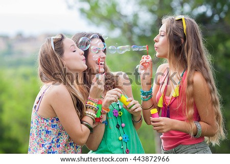 group of girls friends blowing bubbles at music festival