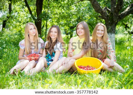 Group of girls gathering strawberry on bright summer day green garden outdoors background. Happy young pretty women having fun smiling. - stock photo