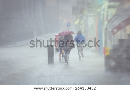 Group of girls hurry at the rain with umbrella in the city - stock photo