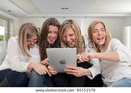 Group of girls laughing looking at a pc tablet in a home interior.