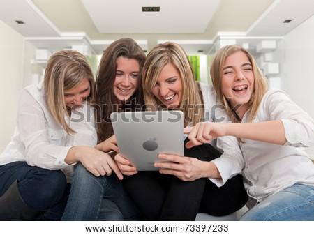Group of girls laughing looking at a pc tablet in a modern interior. Please note that the logo and writing on the tablet are mine. I am attaching a property release, so no copyright issue. - stock photo