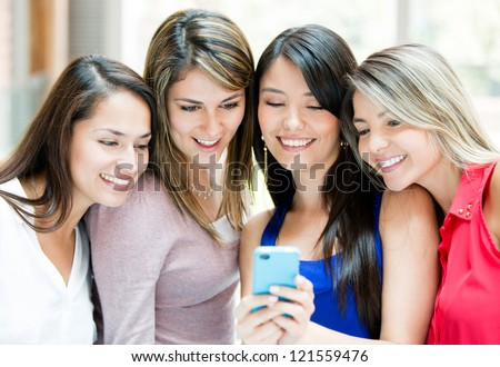 Group of girls looking at a cell phone - stock photo