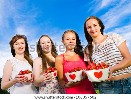 Group of girls smiling and they have full bowl of a strawberries, blue sky on the background, horizontal format - stock photo