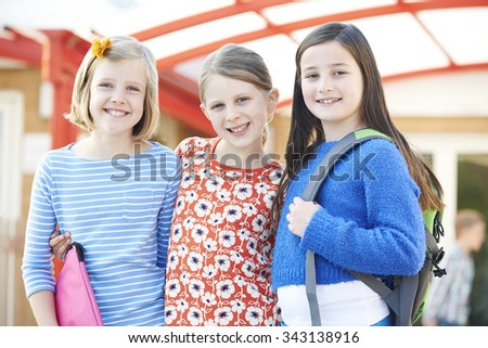 Group Of Girls Standing Outside School With Book Bags - stock photo
