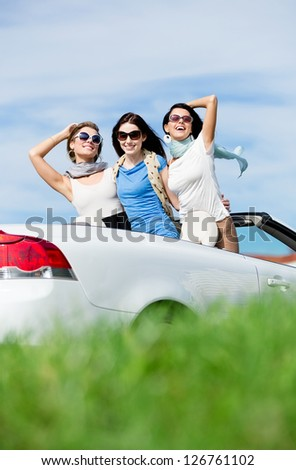 Group of girls stands in the auto with hands up. Happy journey of joyful teenagers - stock photo