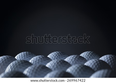 Group of golf balls arranged in lines with empty black copy space for text. - stock photo