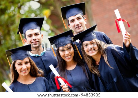 Group of graduate students holding their diploma after graduation - stock photo