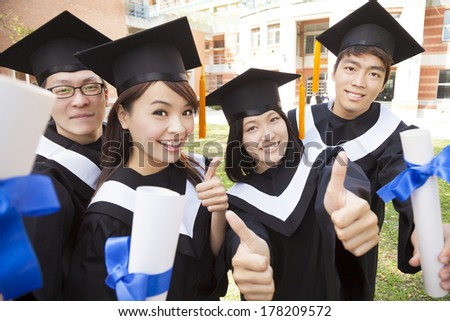 Group of graduating students holding diploma and thumb-up