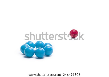 Group of gumballs symbolizing exclusion of one different than themselves - stock photo