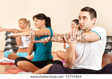 Group of gym people stretching at a gym - stock photo