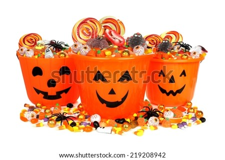 Group of Halloween Jack o Lantern pails with pile of candy over white - stock photo