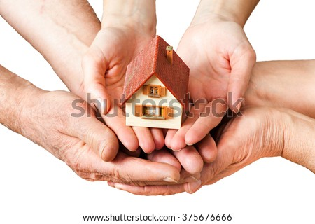 group of hands holding a little house - stock photo