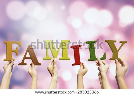Group of hands holding alphabets and arrange a family text, shot with bokeh background - stock photo