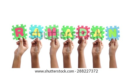 group of hands holding word RAMADAN - stock photo