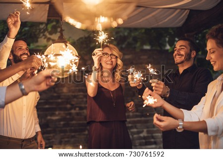 Group of handsome men and pretty women holding sparklers at party and smiling.