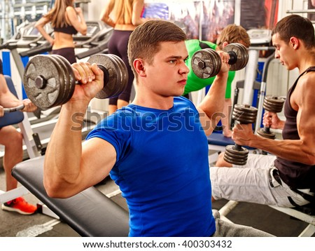 Group of handsome men with strong hands working dumbbells his body at gym.  - stock photo