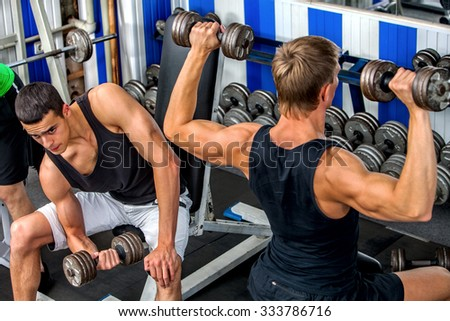 Group of handsome men working with  dumbbells his body at gym.  - stock photo