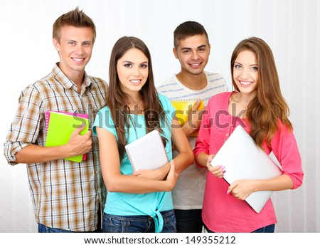 Group of happy beautiful young students at room
