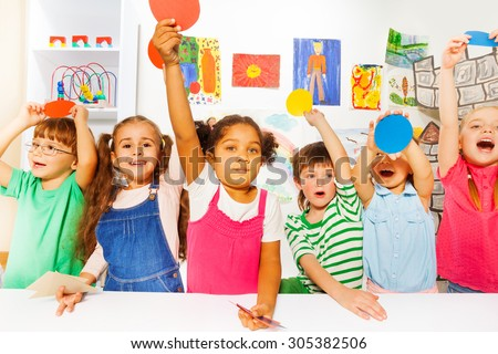 Group of happy boys and girls in kindergarten holding color cardboard shapes and looking at camera
